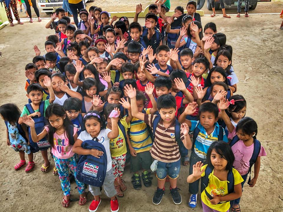 Photo courtesy of ALKFI School kids happily wave after receiving their new bags from Gusto Kong Mag Aral