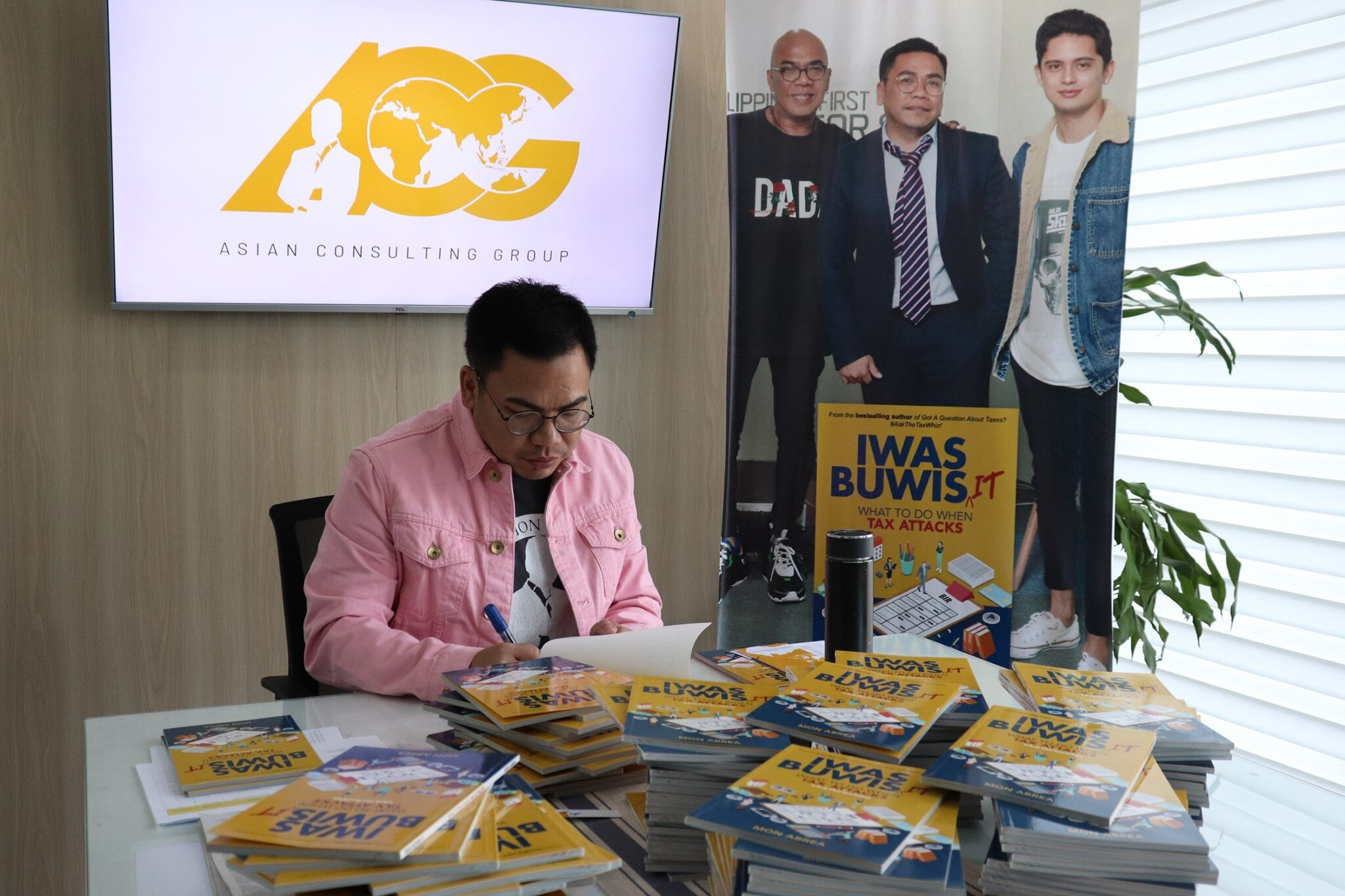 Author Mon Abrea signs copies of Iwas Buwis It book  Photo courtesy of Asian Consulting Group's Facebook page
