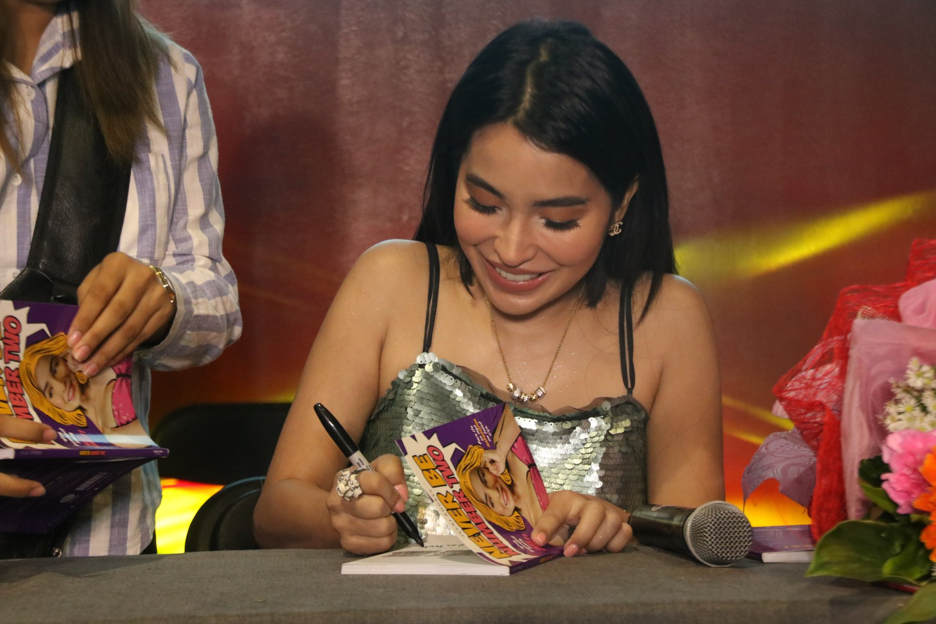 Jelai signing a copy of her book 'Never Be Number Two'
