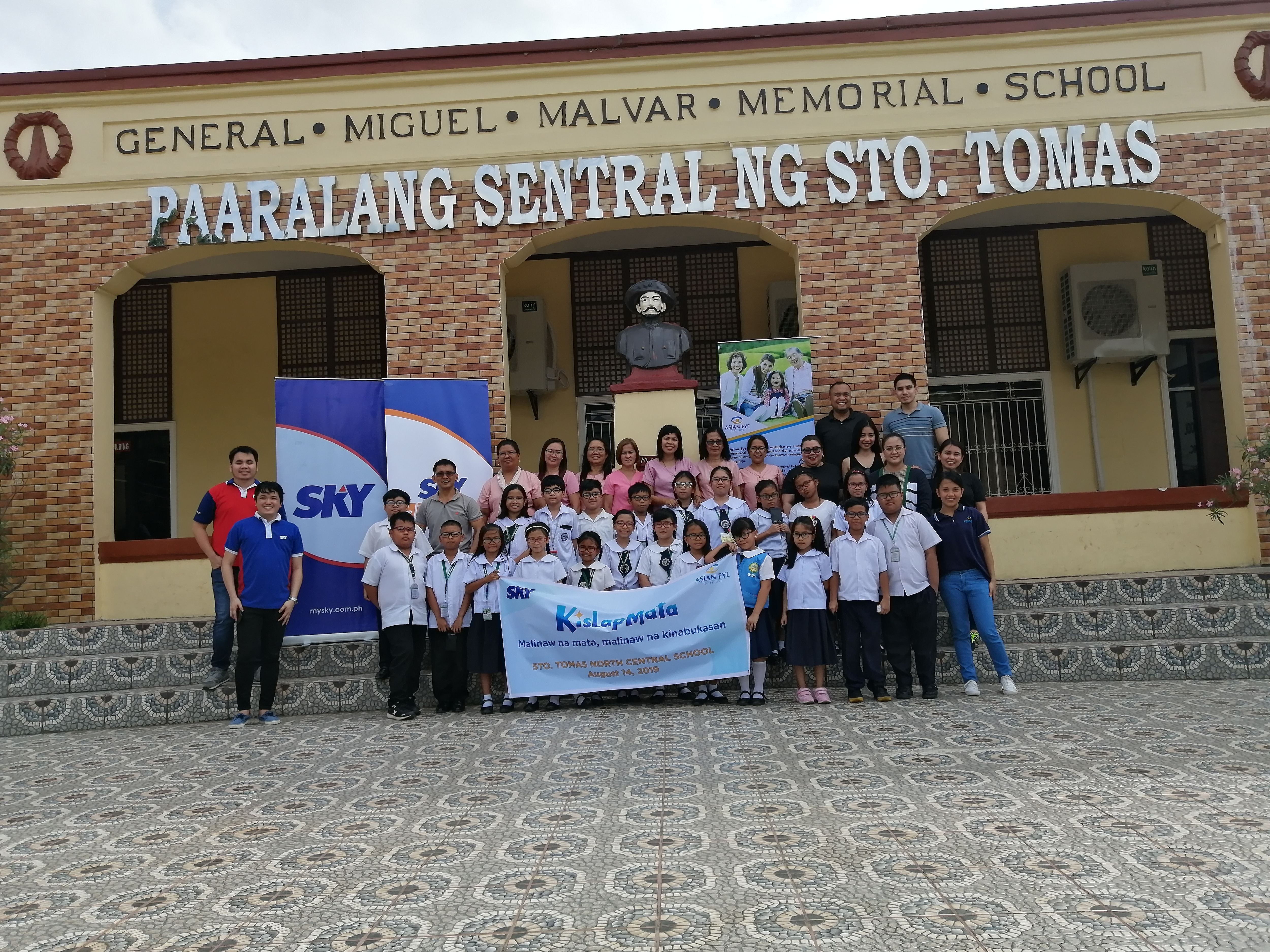 Team and students posing in front of school